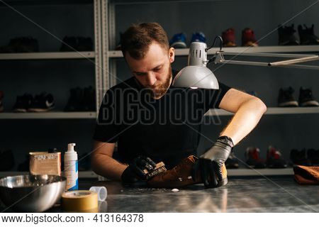Portrait Of Shoemaker In Black Gloves Applying Cleaning Foam On Old Worn Light Brown Leather Shoes T