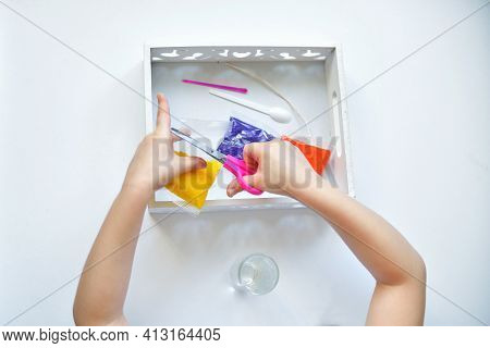 Girl Girl Cuts With Scissors Makes A Candle From Small Paraffin Granules. Kids Pens Are Lying On A W