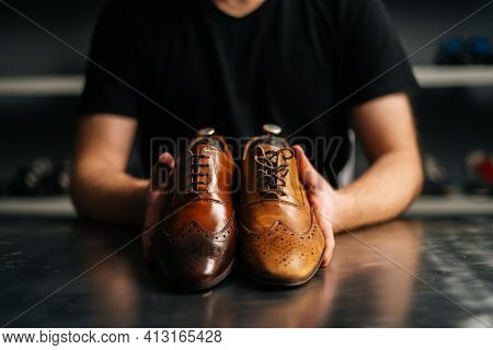 Close-up Hands Of Male Shoemaker Holds Old Light Brown Leather Shoe And Repaired Shiny Shoes After R
