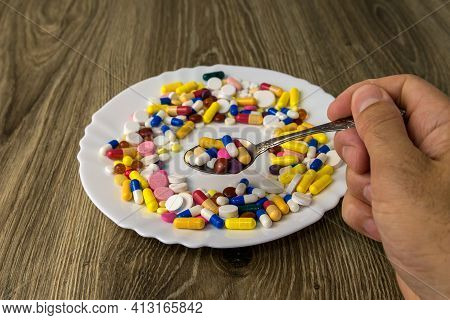 Male Hand Holding A Spoon With Pills On The Background Of A Plate With Pills
