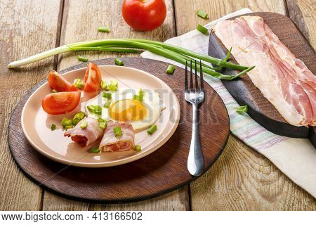 Scrambled Eggs With Bacon With Tomato And Green Onions And On A Wooden Table In A Plate On A Stand W