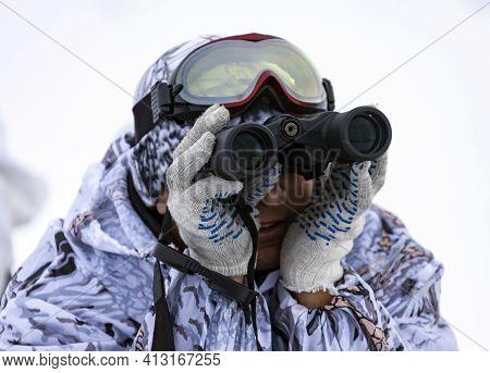 A Man In Winter Camouflage Looks Through Binoculars. Hunter Holds A Pair Of White-gloved Binoculars