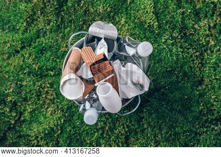 Food Plastic Packaging In Trash Bin On Green Moss Background After Picnic In Forest. Top View. Recyc