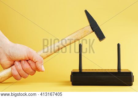 A Hammer Hits The Wi-fi Modem Router To Break It Against A Yellow Background.