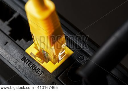 A Yellow Patch Cord Is Inserted Into The Wi-fi Port Of The Router To Access The Internet.