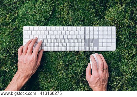 Hands On Laptop Keyboard Over Green Grass, Moss Forest Background. Top View. Mindfulness, Biophilic