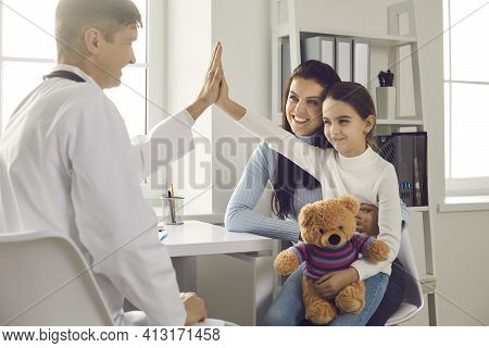Happy Little Girl Patient Gives Five Smiling Male Pediatrician After Medical Examination.