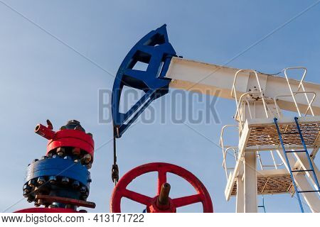 Brightly Colored Oil Pumps Produce Oil Or Gas. Detail Of An Oil Pump Against A Blue Sky.