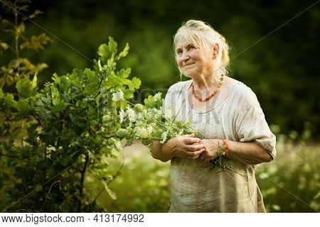Elderly Woman In White Vintage Dress Walks Around The Garden With A Bouquet Of Field Flowers And Smi