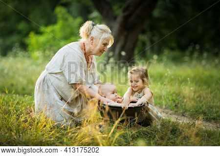 Old Woman And Little Girl Bathe A Baby In A Basin Outdoor