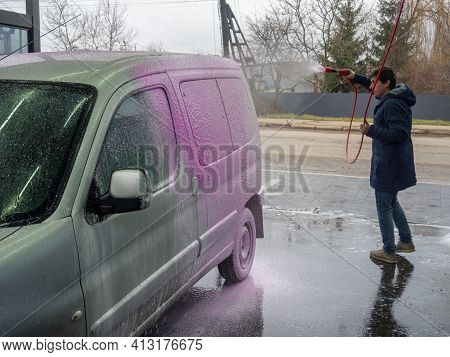 A Man Covers An Auto With Pink Foam At A Self-service Car Wash. Car Wash With A Spray Of Magenta Soa