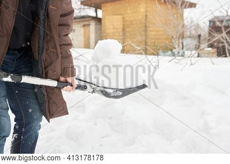 Spring Work In The Garden. A Man Holds A Shovel With A Large Lump Of Snow. He Brings Snow Into The G