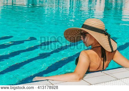Swim Young Woman. Young Sexy Girl In Sun Hat, Bikini Swimsuit, Sunglasses Relaxing In Blue Pool Wate