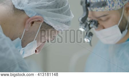 Two Surgeons Work Together In Operating Room. Action. Couple Of Professional Surgeons During Operati