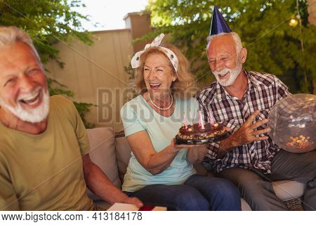 Group Of Cheerful Senior Friends Having Fun At A Birthday Party, Host Of The Party Holding A Birthda