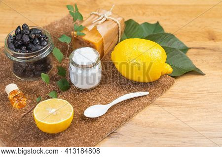 Ecological Natural Cleaning Products On A Wooden Table. Natural Soap, Lemon, Oil, Salt And Dried Ber
