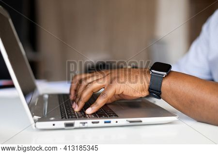 Side Profile Cropped Photo Of Afro Successful Businessman Hands With Fitness Watch, Typing On Keyboa