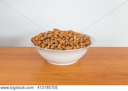 Shelled Almonds (prunus Dulcis) In Bowl On Wooden Table.