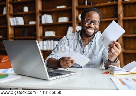 Smiling Black Man In The Office In Anticipation Of The Long-awaited Letter About Work, From Relative