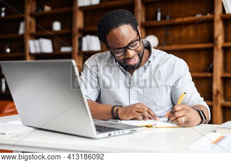 Concentrated Positive Hispanic Man In Eyeglasses Thinking, Taking Notes While Sitting At Table With