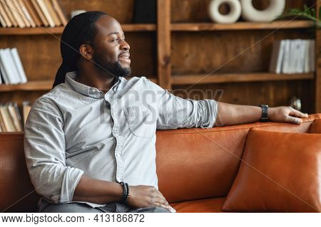 Portrait Of A Young Hispanic Black Man Resting On Sofa, Thinking About The Future, Handsome Positive
