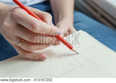 A Pencil In A Woman's Hands. Drawing On Sheet Of Paper With A Simple Pencil. The Concept Of Creativi