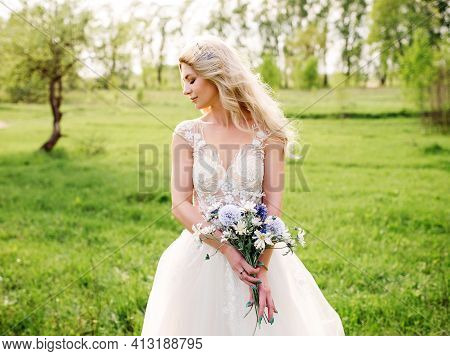 Beautiful Bride In Fashion Wedding Dress On Natural Background.the Stunning Young Bride Is Incredibl