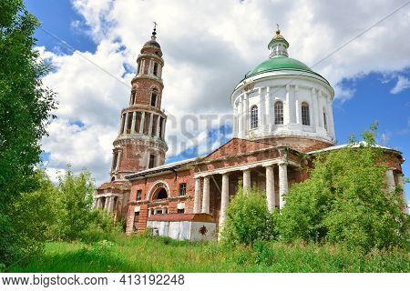 Part Of A Restored Church With A New Dome Against A Cloudy Sky, Surrounded By Greenery
