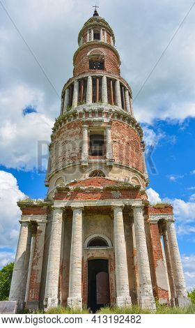 Abandoned Bell Tower With A Cross, Made Of Bricks With Columns Against The Sky, Overgrown With Grass
