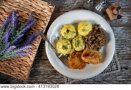 Fried Cod Fillet Served With Boiled Potatoes And Fried Sauerkraut With Mushrooms.
