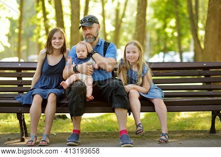 Father And Three Children Having Fun On Summer Day In City Park. Adorable Baby Boy Being Held By His