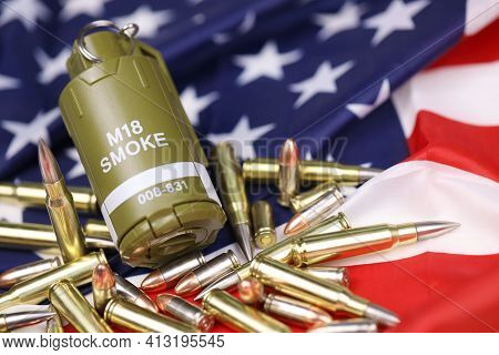 M18 Smoke Grenade And Many Yellow Bullets And Cartridges On United States Flag. Concept Of Gun Traff