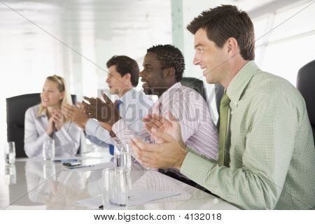 Four Businesspeople In A Boardroom Applauding