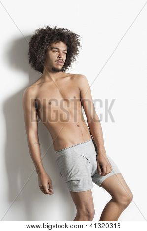 Partially nude young man with curly hair posing over white background