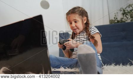 Little Girl Playing Video Game On Gamepad. Kid Dream Stay Home Computer Addiction. Girl Playing Tabl