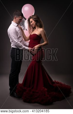 Smiling Young Pregnant Couple Touching Tummy Against Gray Background
