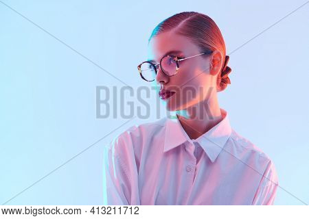 Portrait of a beautiful young woman in elegant glasses and white shirt on light blue background in pink lighting. Copy space. Business style. Glasses fashion.