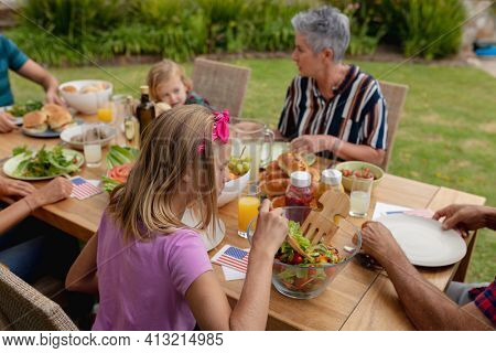 Caucasian senior woman talking with family eating meal together in garden. three generation family celebrating independence day eating outdoors together.