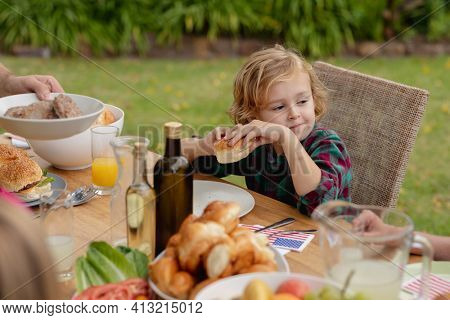 Smiling caucasian boy holding hamburger eating meal with family in garden. family celebrating independence day eating outdoors together.