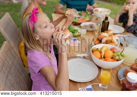 Caucasian girl eating hamburger having meal with family in garden. family celebrating independence day eating outdoors together.