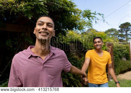 Diverse gay male couple holding hands and walking in garden. staying at home in isolation during quarantine lockdown.