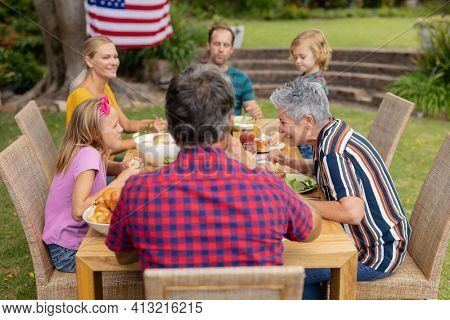 Caucasian three generation family sitting at table eating meal in the garden. three generation family celebrating eating outdoors together.
