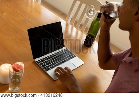 Mixed race man sitting at table making video call and drinking wine. staying at home in isolation during quarantine lockdown.