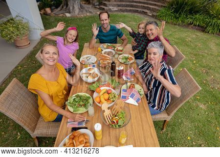 Caucasian three generation family having celebration meal in garden smiling and waving to camera. three generation family celebrating independence day eating outdoors together.