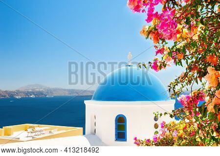 Santorini Island, Greece. Traditional Greek Church With Blue Dome And Tree With Pink Flowers. Famous