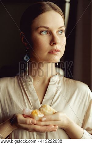 Young European Girl Holding A Gemstone With Boths Hands In Front Of Her. Looking Towards The Camera.