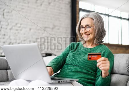 Pretty Senior Businesswoman In Glasses And Green Jumper Sitting At The Desk Using Laptop And Credit