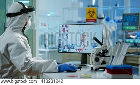 Senior Woman Doctor Offering Medical Online Advices To Chemist In Ppe Suit Using Pc Webcam. Scientis