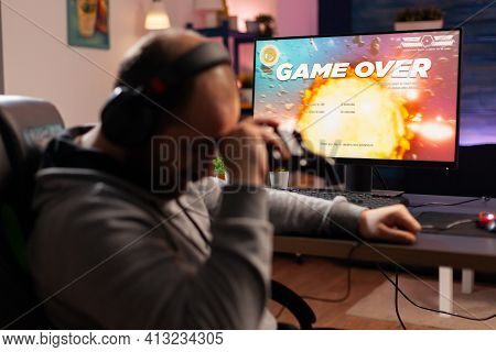 Addicted Gamer Losing Space Shooter Videogame Using Headphones And Wireless Joystick. Upset Player .