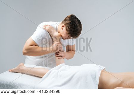 Male Masseur With Strong Hands Massaging Lower Part Of Leg To Young Woman Lying On Massage Table On